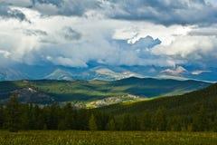 Schöne Ansicht, zu schneien Berge und grünes Feld mit Sonnenlicht und Himmel im Sturm stockfoto