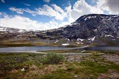 Schöne Ansichten von Schnee-mit einer Kappe bedeckten Bergen und von kurvenreicher Straße herein noch Lizenzfreie Stockfotos