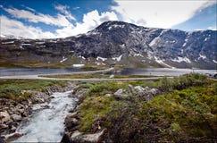 Schöne Ansichten von Schnee-mit einer Kappe bedeckten Bergen, von Wasserfällen und von Wicklung Stockfotografie