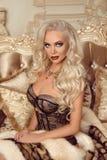 Schöne anziehende blonde Frau in der sexy Wäsche, die auf königlichem sitzt Lizenzfreie Stockbilder