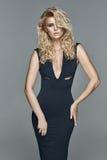 Schöne anziehende blonde Frau in einem schwarzen Kleid Stockfotos