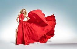Schöne anziehende blonde Frau im roten wellenartig bewegenden Kleid Stockbilder