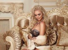 Schöne anziehende blonde Frau in sexy Wäsche- und Pelzmantelposition Lizenzfreies Stockfoto