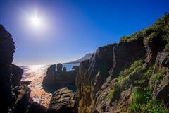 Schöne Anziehungskraft von Kalksteinbildungen am Pfannkuchen-Rock mit Sonnenglanz im blauen Himmel, Punakaiki, Westküste Lizenzfreies Stockbild