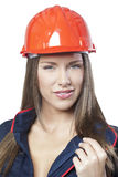 Schöne Arbeitnehmerin im blauen Gesamt- und roten Schutzhelm Lizenzfreie Stockbilder