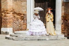 Schöne Aristokratkostüme vor alter Backsteinmauer und Tür in Venedig, Italien stockfoto