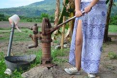 Schöne Asiatin auf einer manuellen Wasserpumpe in einem kleinen Dorf in den Philippinen stockbilder