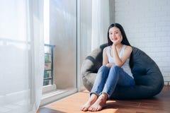 Schöne Asiatin, die auf schwarzem Sofa Relax sitzt stockfotos