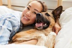 Schöne Asiatin, die Hund umarmt lizenzfreie stockfotografie