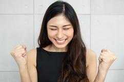 Schöne Asiatin, die oben ihre Hände anhebt stockfoto