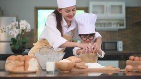 Schöne Asiatin und netter kleiner Junge mit Brillen bereiten sich zu in der Küche zu Hause kochen zusammen vor Lebensstile und Fa stock video footage