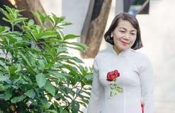 Schöne Asiatin von mittlerem Alter, die in einem weißen Kleid mit einer gestickten roten Rose lächelt stockfoto