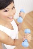 Schöne asiatische chinesische Frau mit Gewichten an der Gymnastik Lizenzfreie Stockbilder