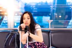 Schöne asiatische Frau betrachtet Armbanduhr nach der Prüfung der Zeit lizenzfreie stockfotos