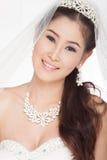 Schöne asiatische Frau des Porträts im weißen Hochzeitskleid mit Schleier lizenzfreie stockfotografie
