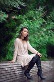Schöne asiatische Frau, die auf der Bank im grünen Park und allein und im Denken sitzt Lizenzfreies Stockbild