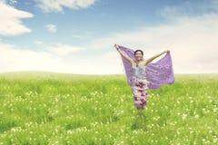 Schöne asiatische Frau, die auf Feld läuft stockbilder