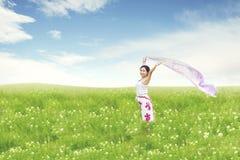 Schöne asiatische Frau, die auf Feld läuft stockbild