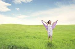 Schöne asiatische Frau, die auf grünem Feld läuft lizenzfreies stockfoto
