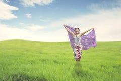 Schöne asiatische Frau, die auf grünem Feld läuft lizenzfreie stockbilder