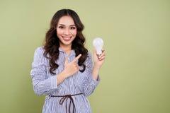 Schöne asiatische Frau, die Glühlampe hält und zeigt Stockfotos
