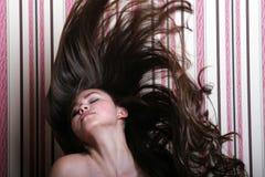 Schöne asiatische Frau, die ihr langes Haar wirft Stockbild