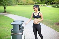 Schöne asiatische Frau, die im Park nach ihrem Lauf aufbereitet lizenzfreie stockbilder