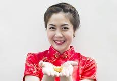 Schöne asiatische Frau, die innen chinesisches Gold anhält Lizenzfreies Stockfoto