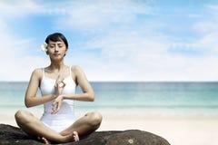 Schöne asiatische Frau, die am Strand meditiert Lizenzfreies Stockfoto