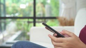 Schöne asiatische Frau, die Zeit genießt und auf modernem Sofa vor dem Fenster sich entspannt in ihrem Wohnzimmer unter Verwendun stock footage
