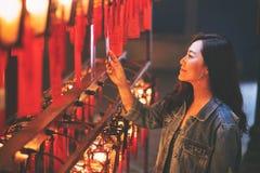 Schöne asiatische Frau genoss, rote Lampen und Wünsche im chinesischen Tempel zu betrachten lizenzfreie stockbilder