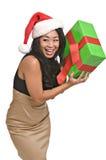 Schöne asiatische Frau hält ein Weihnachtsgeschenk an stockfotografie