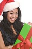 Schöne asiatische Frau hält ein Weihnachtsgeschenk an Lizenzfreie Stockfotografie