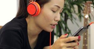 Schöne asiatische Frau hört auf Musikkopfhörer und benutzt Smartphone auf der Couch zu Hause, die Lebensstil sich entspannt stock footage