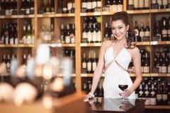 Schöne asiatische Frau mit einem Glas Wein Stockfotografie