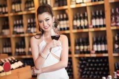 Schöne asiatische Frau mit einem Glas Wein Lizenzfreies Stockfoto