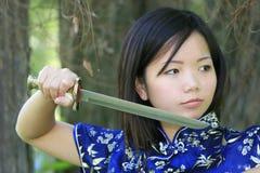 Schöne asiatische Frau mit einer Klinge Lizenzfreie Stockfotografie