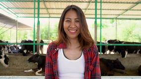 Schöne asiatische Frau oder Landwirt mit und Kühe im Kuhstall auf der Molkereibauernhof-landwirtschaft und Tierzuchtkonzept stock video footage