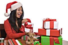 Schöne asiatische Frau wickelt Weihnachtsgeschenke ein Stockbild