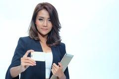 Schöne asiatische Frauenstellung des Porträts, Grifftablette und nameca Stockbilder