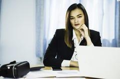 Schöne asiatische Geschäftsfrau des Porträts mit VR und intelligente Telefone auf Tabelle, mit Verkäufen von VR-Kopfhörer in der  stockfotos