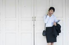 Schöne asiatische Geschäftsfrau, die Handy nennt. stockfoto