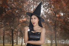 Schöne asiatische Hexenfrau mit Hut unter Verwendung des magischen Bannes Stockfoto