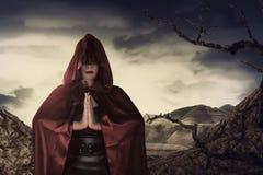 Schöne asiatische Hexenfrau mit rotem Mantel betend Lizenzfreie Stockbilder