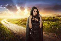 Schöne asiatische Hexenfrau mit schwarzer Haube Stockbild
