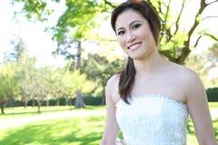Schöne asiatische Hochzeits-Braut im Park Lizenzfreies Stockfoto