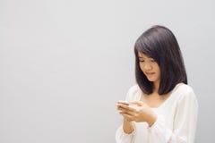 Schöne asiatische junge Frau, die Mobiltelefon, über Betonmauer verwendet stockfoto