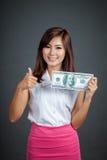 Schöne asiatische Mädchendaumen oben mit einem 100 Dollarschein Stockbild