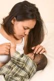 Schöne asiatische Mamma, die ihr Baby stillt Stockfoto