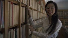 Schöne asiatische Studentin, die das Buch zum Regal setzt stock video footage